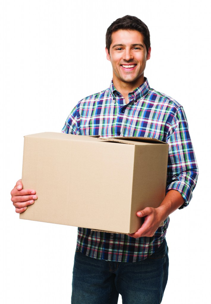 Portrait of a happy young man carrying cardboard box. Vertical shot. Isolated on white.
