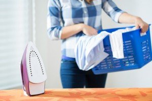 Photo of young woman bringing the clean laundry to iron